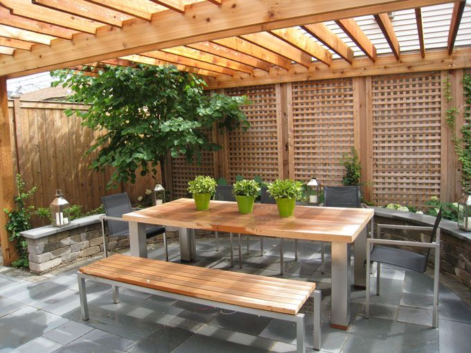 Cedar lattice panels mask the garage siding while a pergola provides filtered light in this contemporary dining space