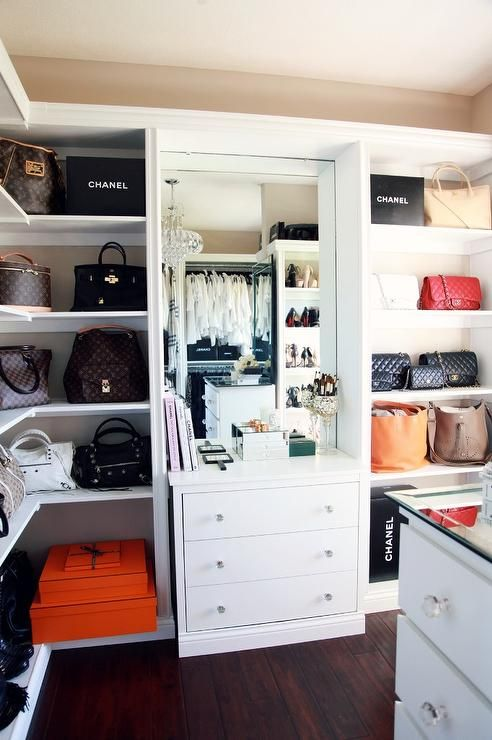 Organized, glam closet features beige walls holding mounted wraparound bag shelves accented with orange Hermes boxes and black Chanel shopping bags flanking a built in white dresser finished with round glass pulls sat below a large mirror.