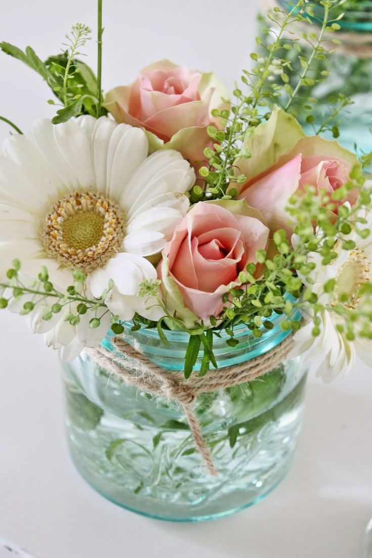 This pretty bouquet made of pink roses and white daisies makes a lovely spring arrangement. A glass jar vase tied w/ a piece of twine is a simple, but classy floral centerpiece.