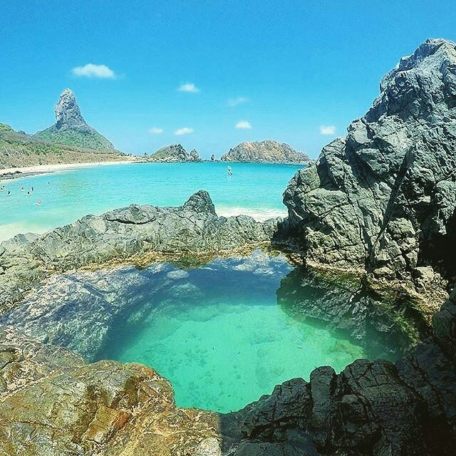 Una piscina natural en Fernando de Noronha (en español: Fernando de Noroña) Brasil. Es un archipiélago volcánico brasileño perteneciente al estado de Pernambuco. Se encuentra en el océano Atlántico a 545 km de Recife (capital de Pernambuco) 710 km de Fortaleza (capital de Ceará) y a 360 km de Natal (capital de Río Grande del Norte). El archipiélago tiene 26 km en total y está formado por 21 islas de las cuales solo está habitada la mayor de ellas (que tiene 17 km) y la cual lleva el mismo…