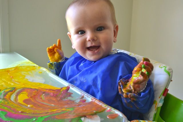 Fingerpainting at 7 months. Use a cookie sheet and edible finger paint.
