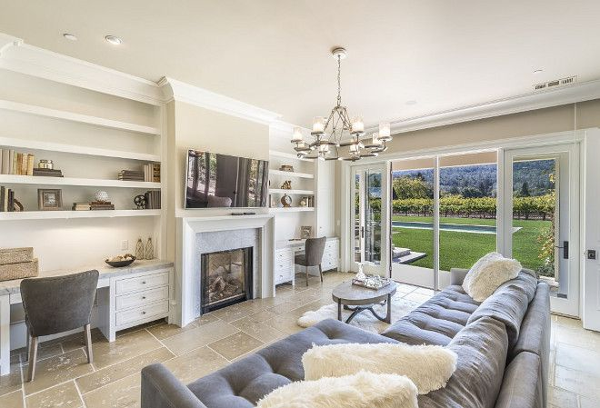 Napa Valley Farmhouse with Neutral Interiors - A cozy den features two built-in desks flanking the fireplace, and sliding doors to the pool area. Notice the stunning view.