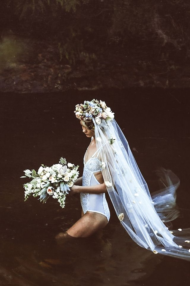 Boudoir shoot in the water with a flower covered veil |