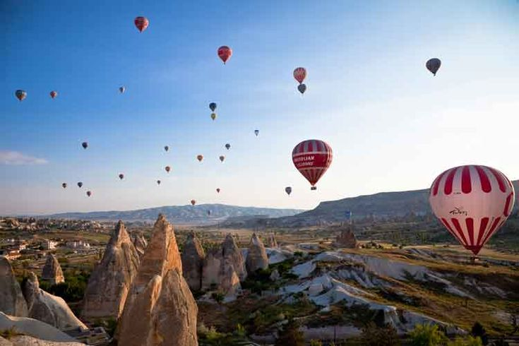 Hot air balloons take off in the early morning light over Göreme town in Cappadocia. Image by Christopher Pillitz / The Image Bank / Getty Images.