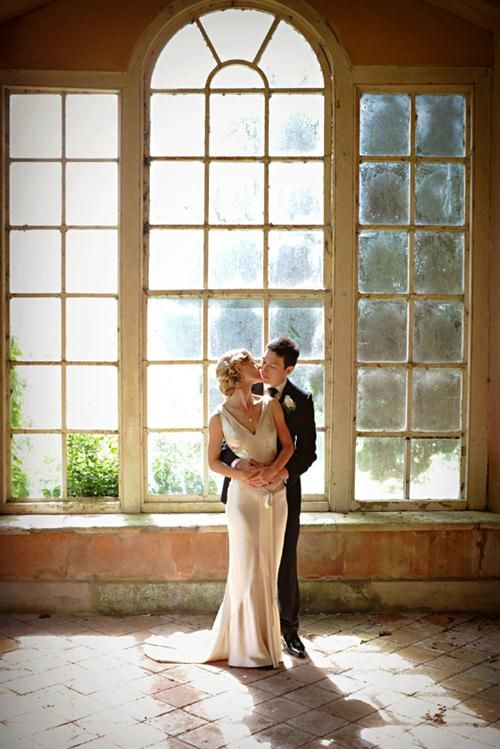 Bride and groom infront of arch window, vintage wedding, Richard Rayner (photographer)