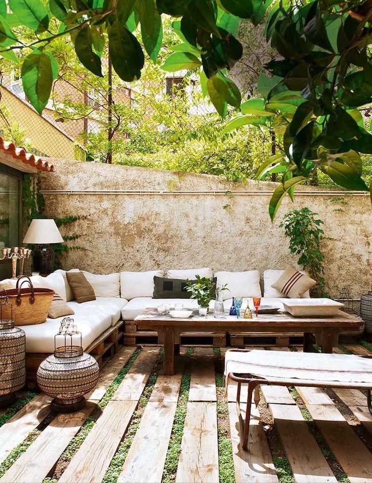 petite cour méditerranéenne aménagée avec un grand canapé d'angle en palettes Euro