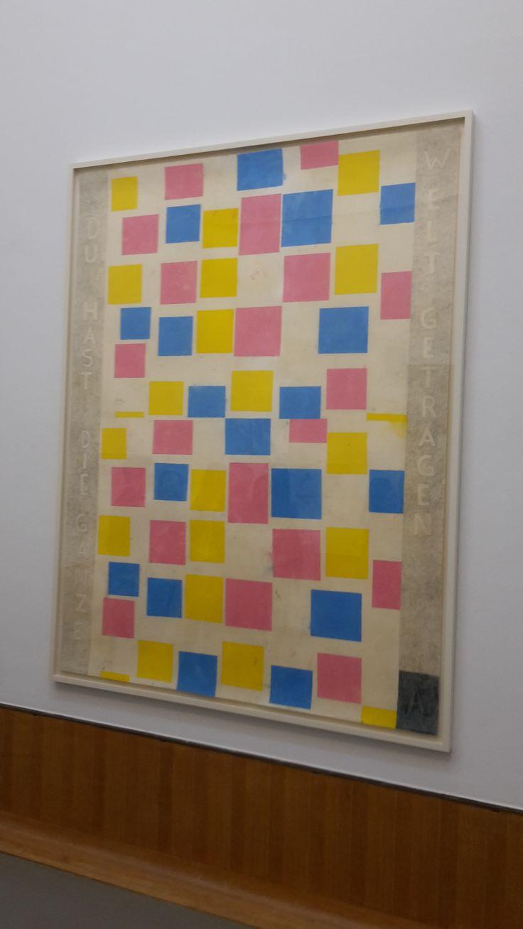 Dit is een schilderij van de kunstenaar Piet Mondriaan. Het heet 'Compositie met kleurvlakjes' en is gemaakt in 1917. In dit jaar werd ook de groep De Stijl opgericht. Het laat de overgang zien van zijn vroegere werk en de latere abstracte compositie. De vlakjes zweven in wit en de vlakjes hebben een beetje gedempte kleuren. Ook heeft hij de lijst beschilderd, zodat het één geheel word.