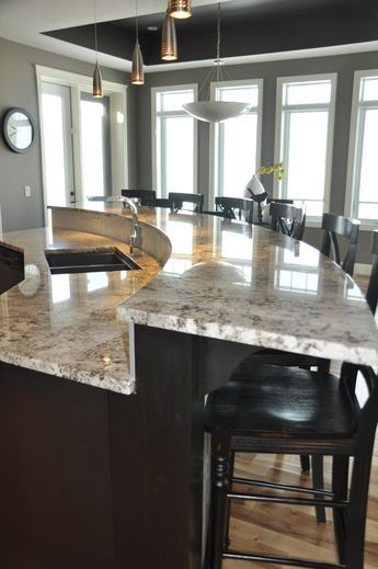Curved Island Bi Level Dark Cabinets Light Countertop