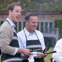 Prince William, left, gets a little smoke in the eye while cooking a BBQ with Prime Minister John Key at Premier House, 2010