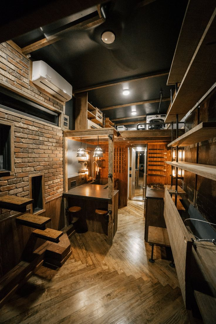 Floating rebar step, herringbone floors, and real brick veneer in this tiny house by Wind River Tiny Homes.