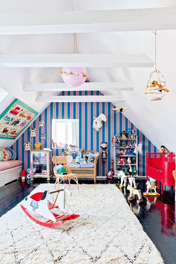 attic turned kid's playroom with one striped wall, art on angled ceiling, lush rug on top of glossy black floorboards