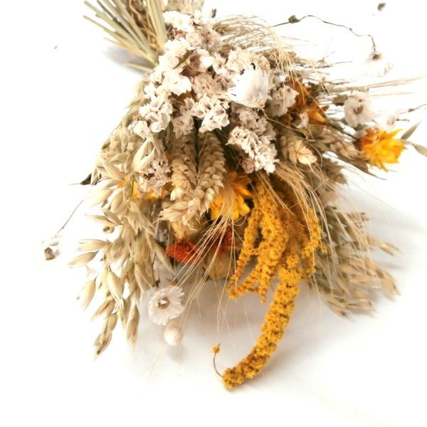 A beautiful bouquet of dried flowers, containing Carthamus, Oats, Rhodante White, Barley, Statice White, Hang Amaranthus - yellow, Setaria - Yellow, Helichrysum yellow and Triticum Natural Wheat. The bouquet is finished off with raffia. This is perfect for a bohemian or rustic wedding day, or an unusual centerpiece for your kitchen dining table. Either use free standing or in a vase.