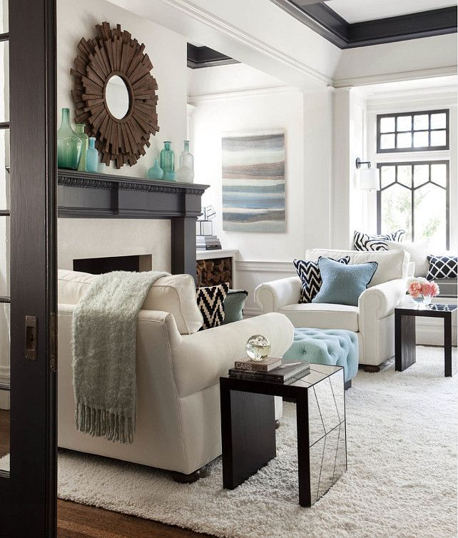 Transitional living room with pops of blue. love the chairs, rug, pillows and ottoman.