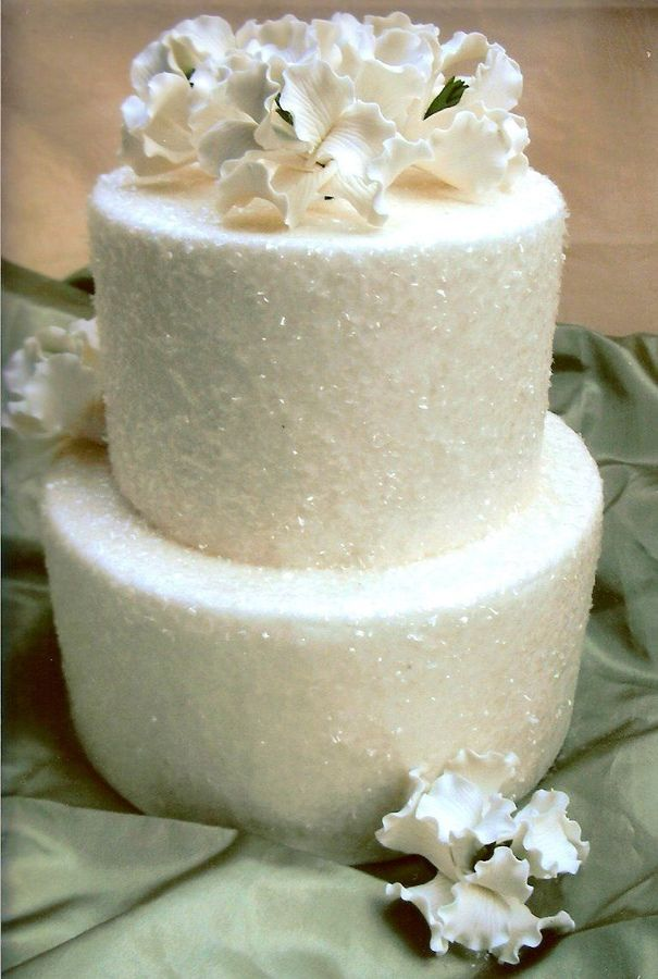 A two tier wedding cakes covered in fondant then coverend in edible glitter and topped with sugar flowers.