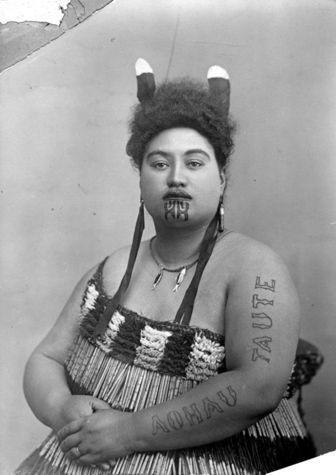 """Portrait of Pikau Teimana of Putaruru, wearing a piupiu and with the words """"Aohau Taute"""" tattooed on her right arm, taken ca 1910 by an unknown photographer. She wears two huia feathers in her hair, and two pendants in the shape of fish around her neck."""