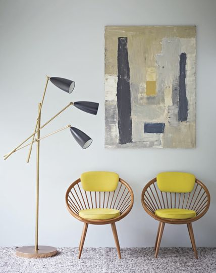 Modern retro chairs with banded seats and yellow cushions, modern art painting on wall, three light free-standing vintage lamp