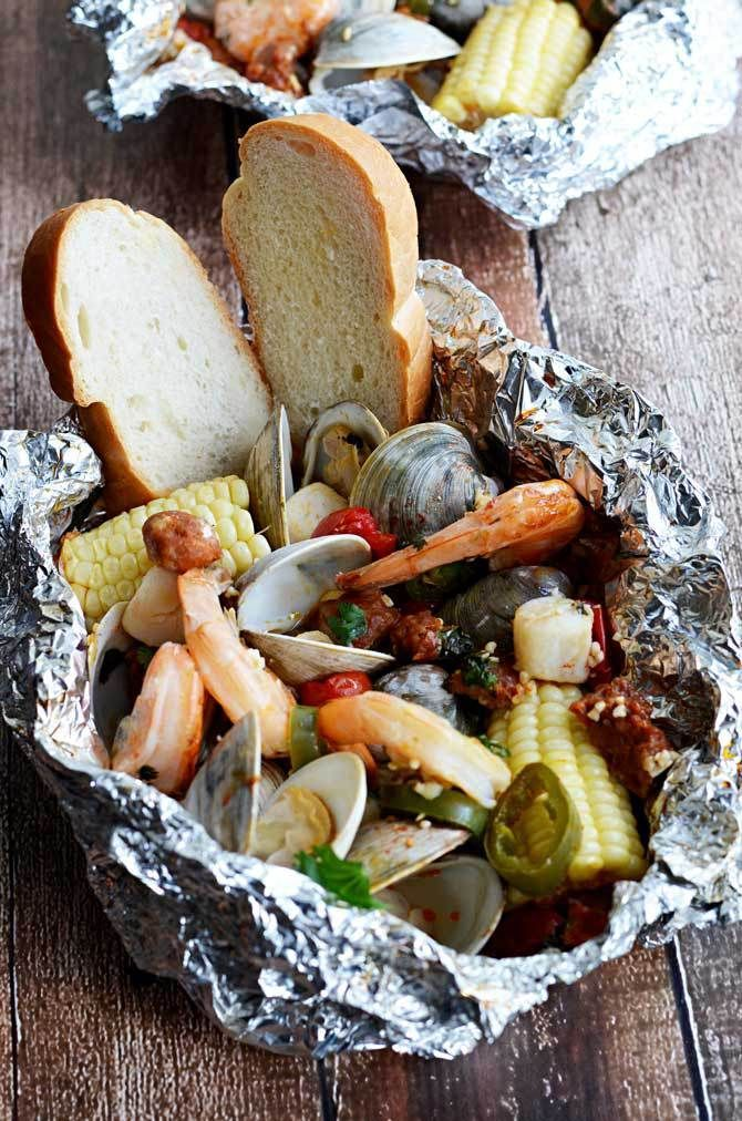 Cilantro-Lime-Garlic Seafood Packets!  These easy-to-make packets are filled with shrimp, clams, scallops, chorizo sausage, corn, and tomatoes!  The seafood and sausage steams in its own juices and mixes with cilantro, lime, garlic, and a bit of butter to create an amazing sauce that you can dip bread in or serve over rice.  The individual packets can be made on the grill or in the oven and are great for parties!  My dad kept calling them THE BOMB Seafood Packets, haha!   hostthetoast.com