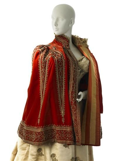 """Charles Frederick Worth: Mantle 1888  """"Its appearance is derived from a man's 16th-century Spanish cape but updated.... Its unexpected contrasting orange and gold striped lining is revealed when the mantle is opened."""""""