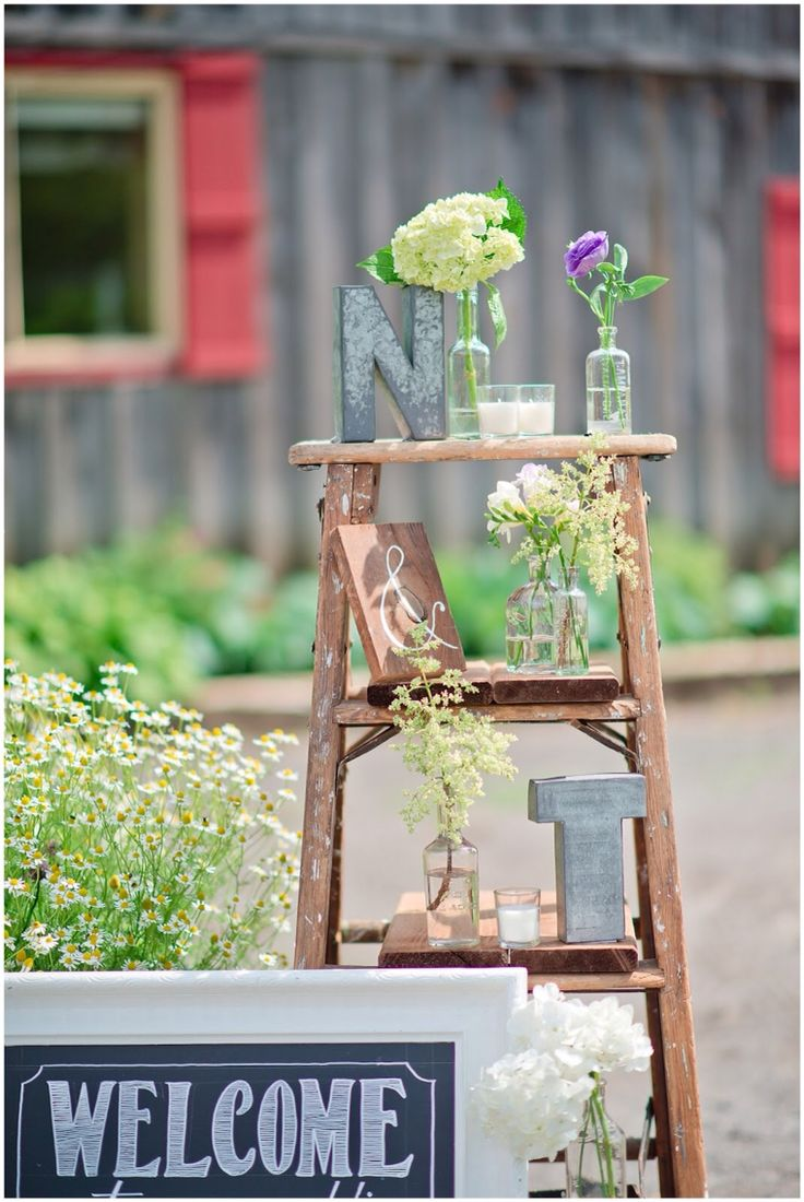 Rustic wedding decor. Antique ladder with flowers.