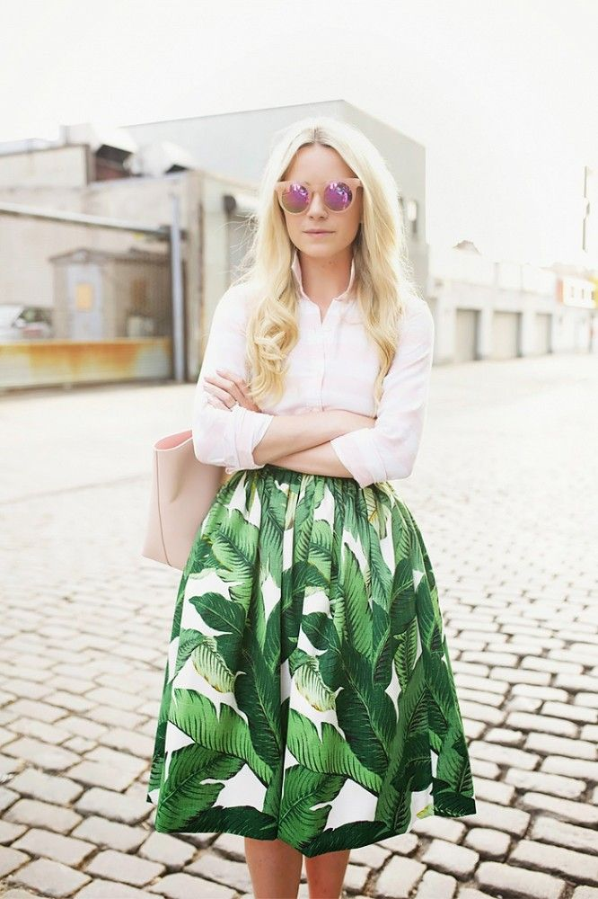 Blair Eadie wears a button-down blouse, palm print midi skirt, blush pink tote, and matching mirrored sunglasses
