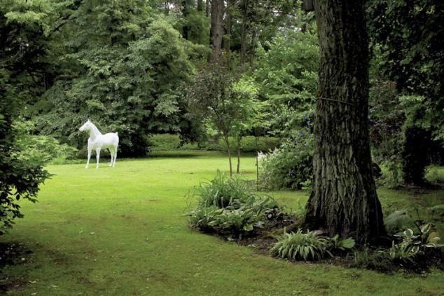 Biały koń w ogrodzie - od razu widać, że w domu mieszka artysta.