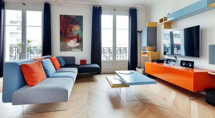Soggiorno contemporaneo moderno con un bellissimo mix di colori: arancione, blu (chiaro e scuro) e grigio, tutto abbinato con il colore del legno dei pavimenti