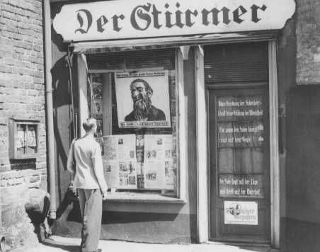 """A young man looks at the antisemitic caricature in the display window of the Danzig office of """"Der Stuermer."""" The poster reads: """"The Jews are our misfortune."""" Danzig, 1939."""