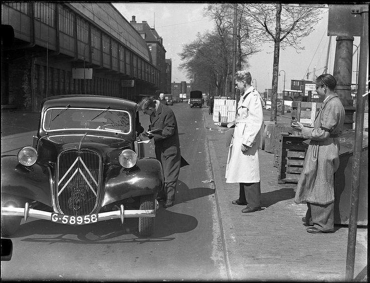 Autotelling (i.v.m. aanleg IJ-tunnel) bij de IJ-pont aan de De Ruyterkade achter het Centraal Station, bestuurder van Citroën Traction Avant wordt geënquêteerd, 19 april 1950. Foto Ben van Meerendonk