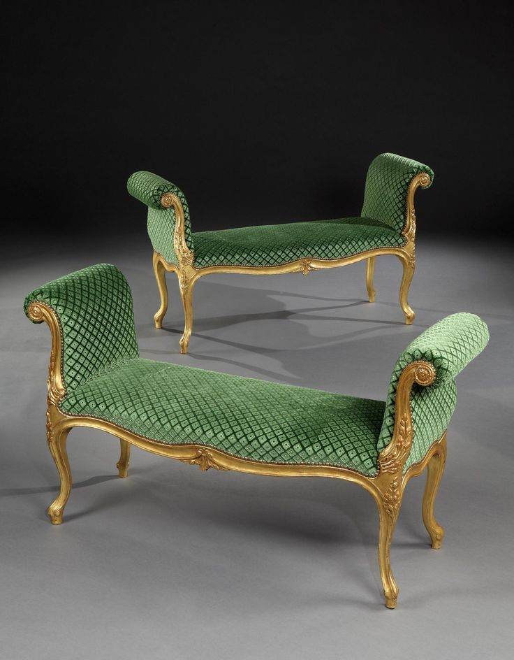 An impressive pair of mid 18th century Chippendale period carved giltwood window seats of generous proportions, each having a serpentine fronted seat upholstered in green silk gaufrage velvet, upright outscrolled arm supports faced with carved giltwood paterae resembling a sunflower, and moulded downswept front with floral carving, having a moulded front rail with central floral motif; on moulded cabriole legs terminating in a French toe. English, circa 1770