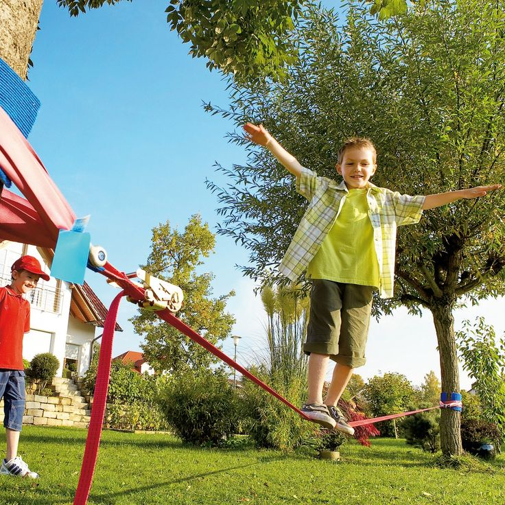 Attaching slack line to two trees. This activity helps children build confidence and develop a sense of trust with you.