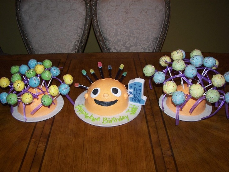 """Eebee Baby cake & cake pops! Eebee head made out of chocolate cake with banana filling, grape licorice for the """"hair"""" with spice gum drops for the colorful tips! Frosting for the head & face, & fondant for the eyes. Cake pops made out of Oreo cookie cake and dipped in melted chocolate & sprinkles! YUM!"""