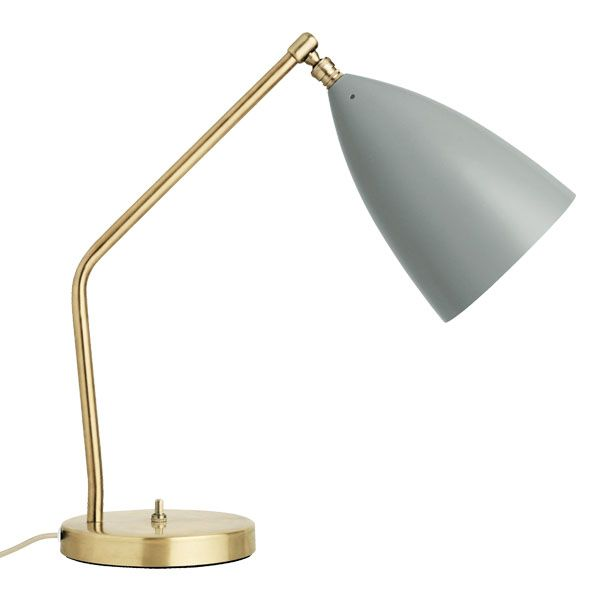 The tubular brass stand of the Gräshoppa table lamp is mounted on a…