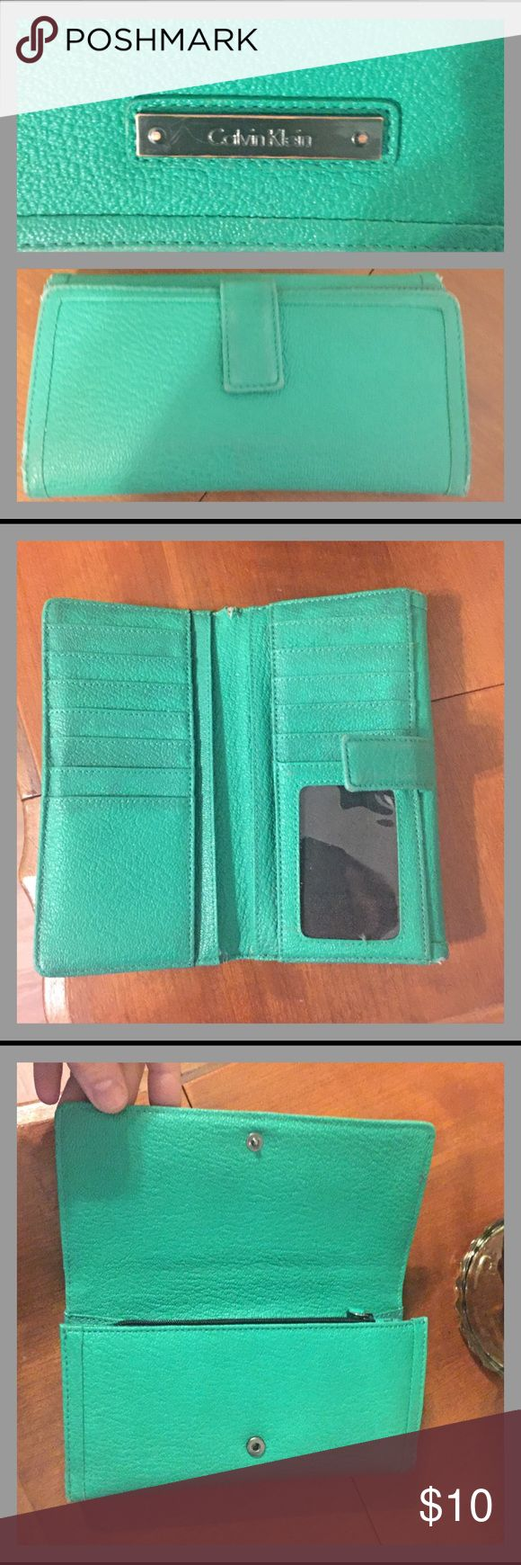 Calvin Klein Wallet Ladies Calvin Klein wallet in green.  Two main compartments - one for cash and change (pic 4) and the other for cash, ID, credit cards, etc (pic 2).  12 credit card slots and one slot for ID.  It's in good pre-owned condition, but there definitely signs of wear.  Some discoloration, especially in the part shown in pic 2.  Also some tearing, as noted in pic 2.  Some signs of wear along the edges of the wallet.  🌟 TOP RATED SELLER 🌟 FAST SHIPPER 🌟 Calvin Klein Bags…