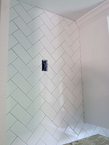 Inexpensive white subway tile laid in a herringbone tile pattern for the backsplash - it was taken all the way up to the ceiling around the range hood.
