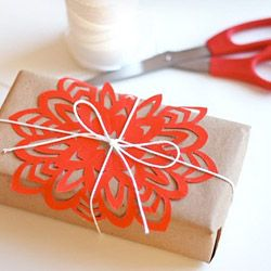 Bright paper snowflake cutouts on plain kraft wrapped gifts tied with string - Moomah the Magazine