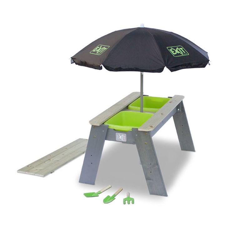 Een compleet plaatje, deze EXIT Aksent zand- en watertafel! Hij wordt geleverd met parasol, een hark en twee schepjes. De houten tafel beschikt over twee groene bakken. Dek die af met het meegeleverde blad en je kunt aan tafel eten of knutselen!