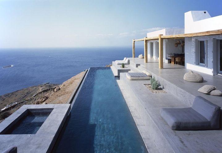 L'area outdoor della villa realizzata a Syros, Grecia, da Block 722 Architects segue la topografia del paesaggio e crea una naturale prosecuzione del living. Piscina a sfioro e solarium panoramico