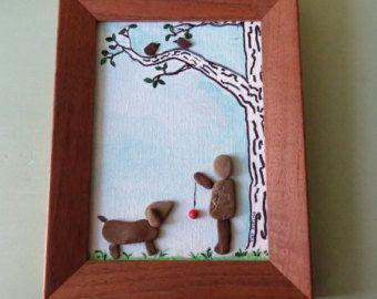 Deze kleine ingelijste originele pebble kunst foto beschikt over een gekooide vogel opknoping van een boomtak op doek. Twee vogels zitten op de tak en een zwarte kat zit onder de boom kijken. De afbeelding is ingelijst in een gerecycleerde eiken frame. De ingelijste foto maatregelen 9 1/2 x 7 1/2.