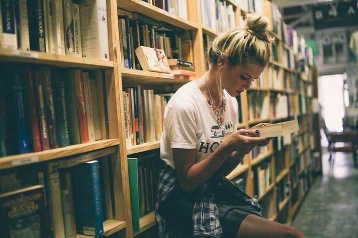 chica en una biblioteca leyendo un libro