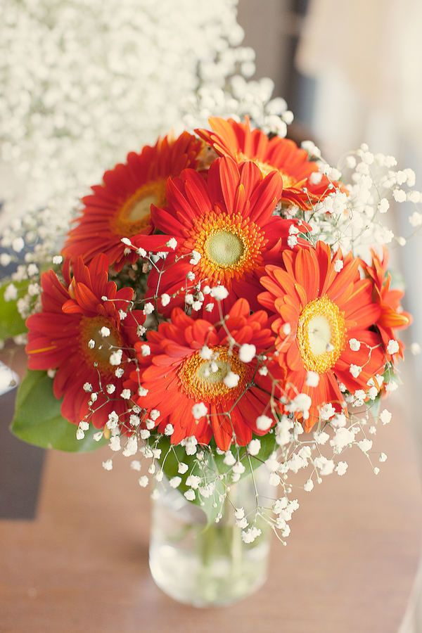 """There's something so frank and honest about gerberas and nothing says """"fall wedding"""" like their fiery orange blooms. A modern option for a tablescape or an easy component of a bouquet, these flowers will stand out in the best possible way."""