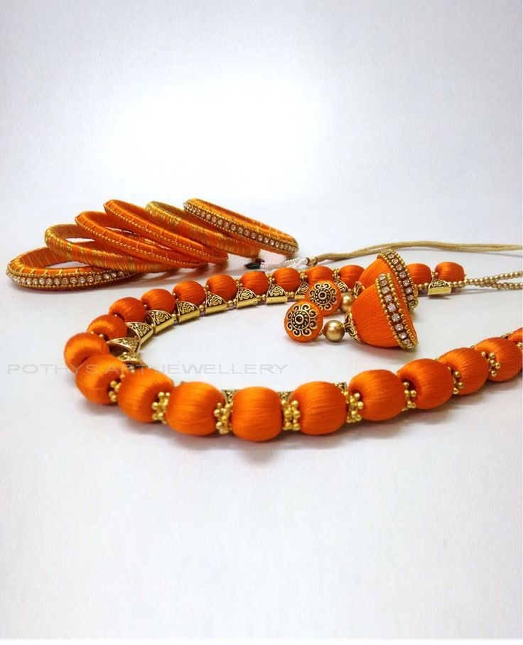 Image via - Pothys website: The necklace set comes along with matching bangles and earrings. Note: Material - Silk Thread, stone colour - silver.  Stone Colour : Silver