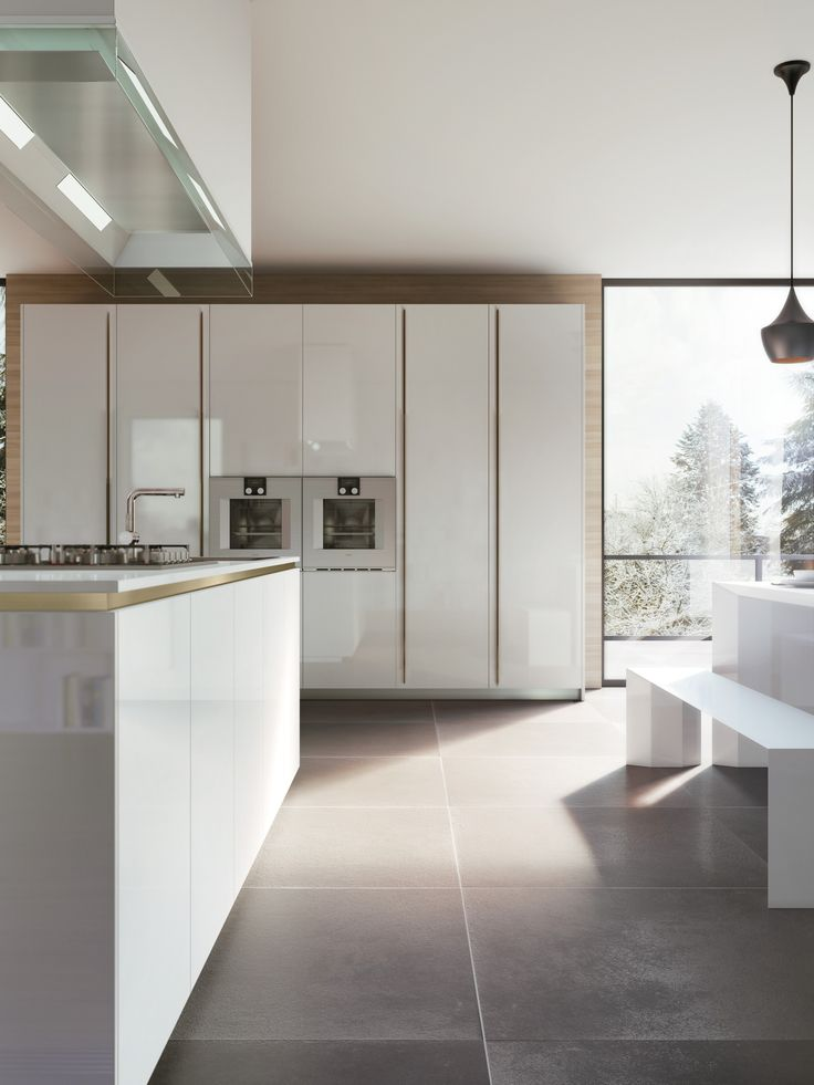 Modular kitchen with a refined contrast between the white lacquered finish and the bronzed metal color for grooves, socles and handles.