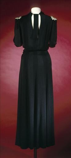 """Evening Dress (back view), Jeanne Lanvin, France: 1937, Robe en crêpe de soie noir, grappe de raisin en pâte de verre transparent et vert.    Label: """"Jeanne Lanvin / PARIS / 15. UNIS FRANCE. 7"""""""