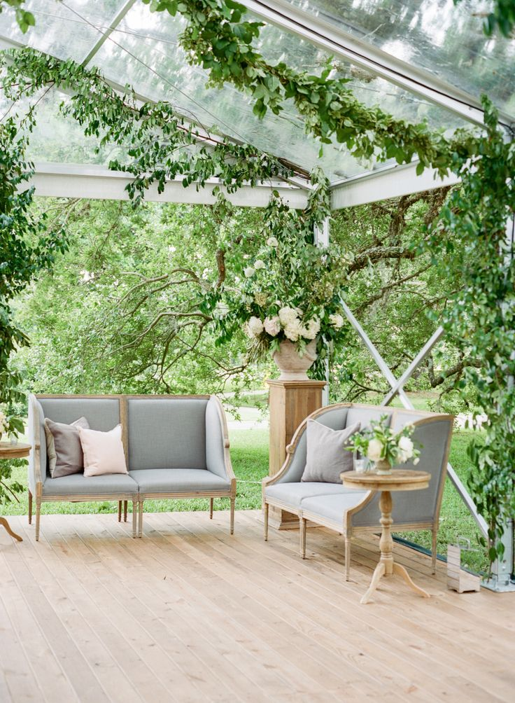 greenery garland draping the ceiling on a clearspan clear roof tent | vintage look furniture lounge | wedding decor