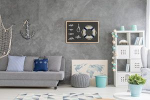 Grey home interior with nautical wall decor sofa carpet and white storage unit