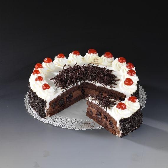 Tort Czarny Las Dwie warstwy delikatnego czekoladowego biszkoptu przełożone kremem o intensywnym smaku czekolady wzbogaconym wiśniami nasączonymi alkoholem. Całość udekorowana śmietaną, kandyzowanymi wiśniami i wiórkami czekolady.