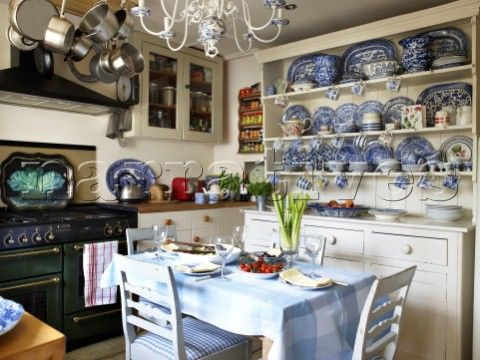Wonderful Country Kitchen. Decorative chinaware in kitchen dresser with set table and pan rack in Gloucestershire home  in  England.