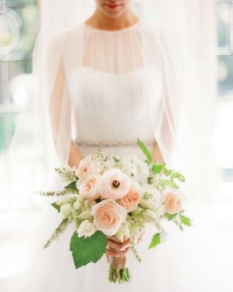 "Garden roses, ranunculus, and blushing bride proteas kept the bouquet by McKenzie Powell ""a little bit wild,"" Bomi says."