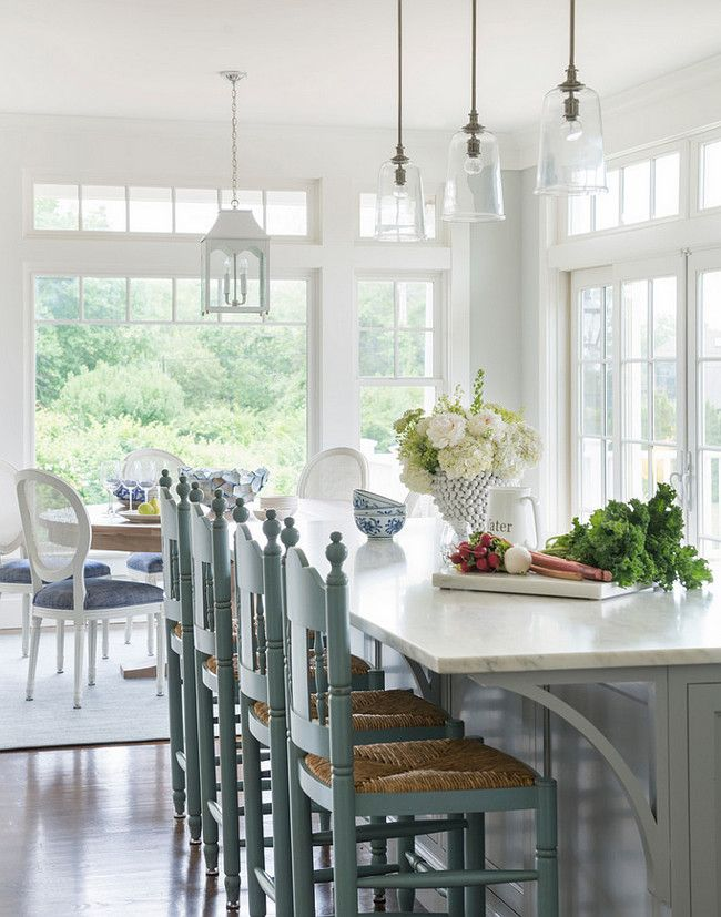 Gray Kitchen Island. Cottage kitchen features three glass pendants illuminating a gray kitchen island topped with white marble lined with turquoise blue counters tools with rush seats. #Kitchen #Gray #KitchenIsland Digs Design Company.