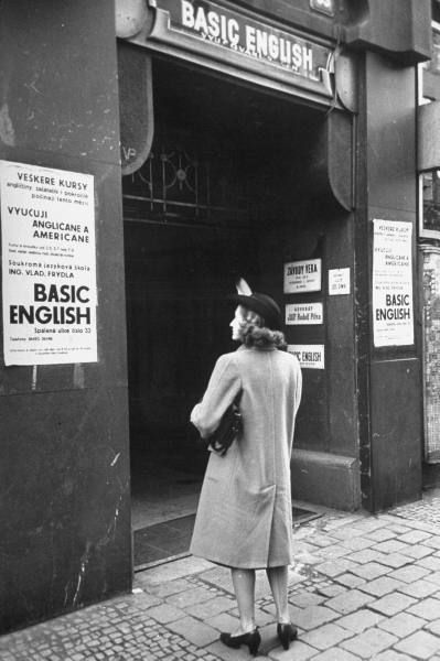 A woman reading the sign outside of the Basic English class. Photograph by Walter Sanders. Prague, Czechoslovakia, December 1947.